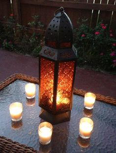 Moroccan lantern surrounded by candles (votives with floating orchids or dahlias?)