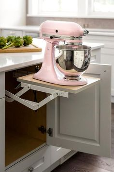 A pink KItchenAid Mixer sits atop a pop up shelf fixed beneath a white island finished with white cabinets adorned with polished nickel knobs.