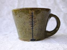 This mug was handmade using stoneware clay and high fire, nontoxic glazes. The body of the mug was first thrown using a pottery wheel. After the mug was trimmed and the handle was attached, the trees were carved into the body of the clay. Once the mug was totally dry, it was baked in