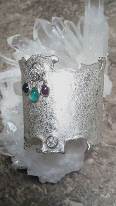 Sterling Silver with a unique micro hammered design  ...diamond set in 14k white gold, ruby, sapphire and a Colombian emerald ....