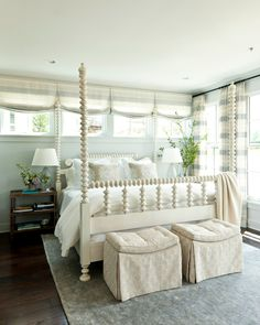Window treatments in a bedroom with a wall of windows behind the bed