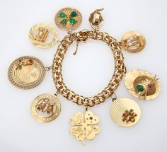 14K yellow gold bracelet suspending nine various 14K yellow gold charms, 7.5'', 63 gms, est: $1200/1800 *Price Realized: $1,680.00