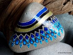 tribal rain. painted rock (sea stone) from Cape Cod. A beautiful stone worn extrememly smooth over time being tumbled in the sea. The colors on this sea stone are indigo, cerulean blue, turquoise, black, gold and white in layers of water resistant glaze inks over paint. This stone has a light weight, calming weight and feels gentle when held. This stone would be perfect placed on a desk or drawing table, nightstand, coffee table, beside a framed photo, on a window sill, alter or grouped…