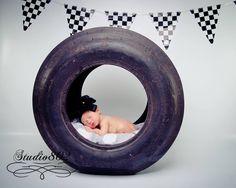 Newborn photography! Sweet baby girl in daddy's racing tire! ©Studio802