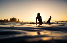 From the 'Sense of Place' category, a couple paddle out for a sunset surf in the coastal surfing town of Byron Bay, Australia.