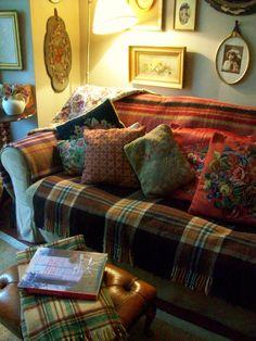 Lovely tapestry cushions + tartan rugs.