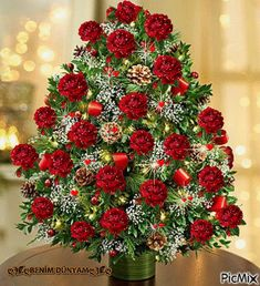 Holiday Flower Tree®️️ Luxury - three dozen fresh red or multicolored roses, baby's breath, boxwood and assorted Christmas greens is in a glass vase, decorated with ornaments and lights. Full-size arrangement measures approximately x Christmas Flower Arrangements, Christmas Flowers, Beautiful Flower Arrangements, Floral Arrangements, Christmas Tree, Flowers Nature, Pretty Flowers, Cemetery Flowers, Flowering Trees