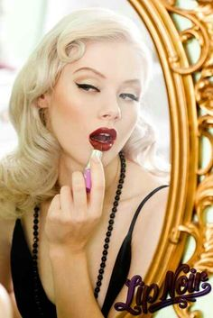 Finger curl, thick liquid eyeliner, penciled eyebrows, red lip burlesque glamour