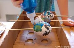 Here's a simple trick for decorating blown eggs:  Thread a skewer through the hole and make notches in the sides of a box lid for the skewers to rest in.  This way, the eggs can easily be turned for decorating.  (From Tinker Lab Blog)
