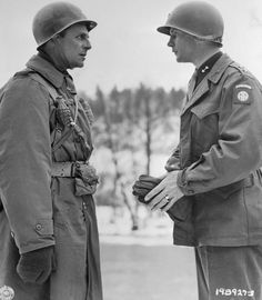 """Major Generals Matthew Ridgway and James """"Jumping Jim"""" Gavin confer during the Battle of the Bulge. It was Gavin's paratroopers who put up stiff resistance to the German onslaught and effectively held the line. Note how Ridgway has grenades hooked to his harness (as well as a shoulder holster, only the cross-chest strap of which is visible), as was his custom. The chance of a Major General needing grenades was unlikely, but the gesture definitely added a warlike persona to the commander."""