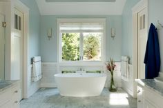 A floor-to-ceiling window affords a view of the surrounding Martha's Vineyard property and can either be opened to enjoy a breeze off the ocean or covered with shades for extra privacy. Marble is used on the floor, backsplash and countertops to create a unified luxe effect in this master bathroom.