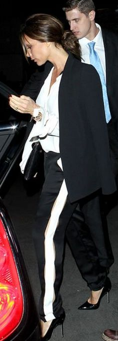 Who made  Victoria Beckham's white button down top, black pants, watch, and black pumps?