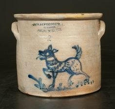 """Rare Two-Gallon Stoneware Crock with Cobalt Dog Decoration, Stamped """"W A MACQUOID & CO / NEW-YORK. / LITTLE WST 12TH ST.,"""" circa 1870, cylindrical crock with tooled shoulder, semi-squared rim, and applied lug handles, decorated with a large brushed design of a dog with lolling tongue, striped body, and spotted haunch, trotting along a grassy lawn. Desirable figural motif. One of the more elaborate dog designs found on American stoneware"""