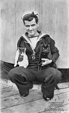 portrait of AB Raymond Stewart Haig on board HMAS Melbourne holding two ship's cats.