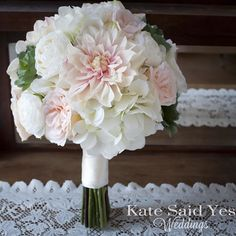 Succulents are a romantic nod to spring in this silk peach and white dahlia garden rose ranunculus and hydrangea wedding bouquet. By Kate Said Yes Weddings