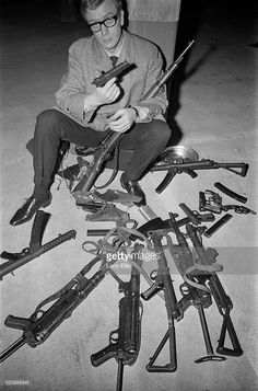 English actor Michael Caine sitting with an array of guns during the filming of 'The Ipcress File', 13th October 1964.