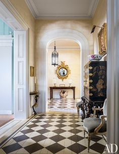 As seen from the entrance hall, a Regency mirror from Mallett is mounted in the stair hall, above an 18th-century table from Florian Papp.  DESIGNER: Mario Buatta PHOTOGRAPHER: Scott Frances