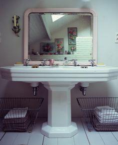 giant pedestal twin sink with pink mirror in modern bathroom