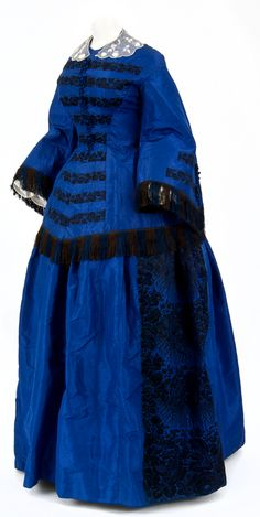 Dress worn by Abby Newell at her wedding to Arthur H. Mills held at Fort Snelling on October 24, 1857. Both jacket and dress are blue taffeta with black brocade trim. The jacket has horizontal bands of black brocade across the front and black and brown fringes along the waist and cuffs. Five blue silk flower shaped buttons fringed with black beads and blue silk balls adorn the front, with two on each sleeve. The skirt is adorned with black brocade in a floral design. Handmade and fully…