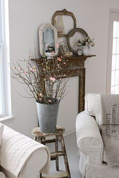 Decorating extras--Rustic frames and spring blooming branches give texture and life to this neutral living room.