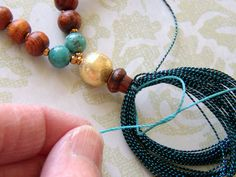 Tie the tassel to the Mala Prayer Necklace.