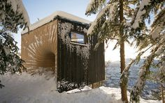 Norwegian mountain hut is entered through a curving orifice