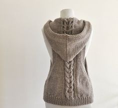 The chic and comfortable hooded vest is handknitted with wool yarn. It is not itchy. It feels soft and pleasant.  So cozy and fashionable!  Size: