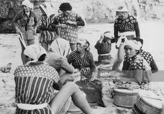 A group of Japanese skin divers or 'Amas' prepare for a day's work near the small fishing village of Onjuku in the Chiba prefecture of Japan, August 1959. Stripped to the waist, they will fill their tubs with the seaweed they harvest.