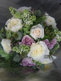 I've used lots of lovely seasonal materials in this trial wedding bouquet designed for a late August wedding, I included Poppy Seed Heads, Blackberries, Champagne Grass, Eryngium, David Austin Rose Patience, Memory Lane & Cream Vendella Roses, Pale Green Classic Hydrangeas, Lily of the Valley or White Lilac and Albiflora Bruneii.