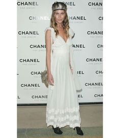 """At the Chanel Fine Jewelry event, """"Nuit de Diamants,"""" Erin wore a long white dress by Chanel, obviously. She accessorized the flowy, girly gown with boho touches—a tribal feathered headpiece and feather-embellished bag.   - MarieClaire.com"""