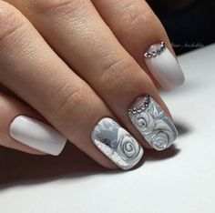 A very pure and wonderful looking winter nail art. The nails are painted in all white and and silver colors. The rose details above the base colors are also painted in white with silver beads as embellishments.
