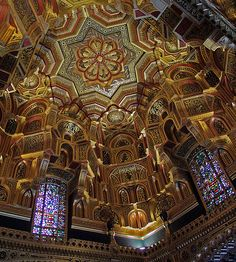 Richly ornate decorations on the ceiling of the Arab Room in the apartments of Cardiff Castle, Wales    The bold geometric designs covered in gold leaf and beautifully matched with stained glass windows.  John Marquess of Bute built it in 1881 and William Burgess designed it.