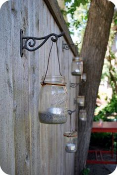 :: Mason jars filled with sand and tea lights hung by twine on wrought iron plant hangers. So many possible variations!