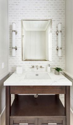 Chic powder room is equipped with a brown vanity finished with a shelf, polished nickel pulls, and a white marble countertop fitted with a sink paired with a polished nickel faucet mounted to white and gray mosaic wall tiles beneath a polished chrome mirror flanked by white glass and nickel wall sconces.