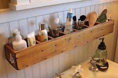 Pequenos nichos de madeira de demolição organizam os cosméticos do banheiro, para quem tem pouco espaço na pia.