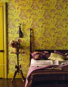 Yellow painted door with yellow and aubergine wallpaper and aubergine and lilac bedlinen.