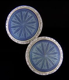 Elegant cullfinks with regal blue enamel centers and stiking Art Deco borders crafted in white gold.  Beneath the translucent blue enamels are engraved designs of starbursts or radiant flower heads.  The color of the enamel highlights the depth of the engraving and throws it into dramatic relief  -  a technique known as guilloche enameling.  Created by Krementz & Company in 14kt gold,  circa 1925.