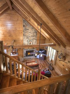 The balcony in this Hochstetler Log Home overlooks a spacious great room with cathedral ceiling, exposed beams, and a floor-to-ceiling stone fireplace mantel. #loghomes #logcabins #exposedbeams #loghome #logcabin