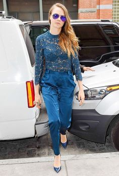 Cara Delevingne wears a blue lace blouse, silk trousers, pumps, and mirrored aviator sunglasses