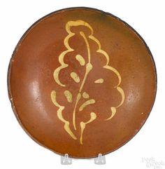 Pennsylvania redware plate, 19th c., with yellow slip leaf decoration, 10'' dia. - Price Estimate: $400 - $800