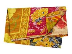 This vibrant and colorful throw is hand-quilted in a reversible design from vintage reclaimed Indian sari textiles