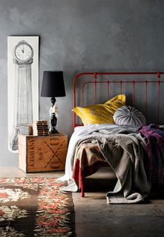 layered bedding - vintage iron bead frame painted - tea chest bedside table - concrete rendered wall