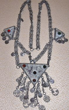 Silver necklace of a lower silver quality. Kurdish, from Iraqi Kurdistan, ca. 1900-1950. With three triangular 'hamay' (amulet box), adorned with coloured glass paste. (Source: Peter Hoesli).