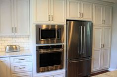Dura Supreme Cabinetry and KitchenAid built-in microwave single built-in wall oven and bottom mount refrigerator.