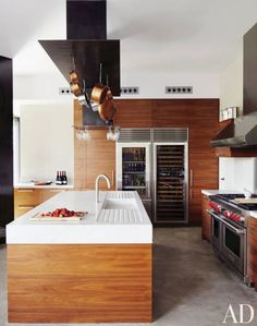A contemporary kitchen in Spain by Olson Kundig Architects is clad in wood panels and features a custom pot rack.