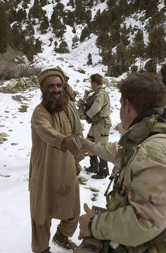 A U.S. Navy SEAL talks to local Afghanis while conducting a sensitive site exploitation mission. #americasnavy #usnavy navy.com