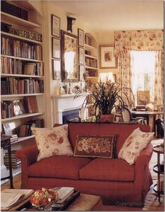 Living room with red sofa and bookcases in the alcoves next to the fireplace