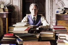 In a still from The Bookshop, Mr. Brundish (Bill Nighy) sits at a desk covered in and surrounded by books. Ordeal By Innocence, Elizabeth Bishop, Bill Nighy, Desk Cover, Big Crush, First Art, Movies Showing, Novels, This Book