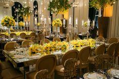 Decoração sofisticada e clássica no hotel Copacabana Palace, no Rio de Janeiro, com paleta de cores em tons de amarelo, dourado e preto. Destaque para os arranjos florais altos e velas penduradas no teto.