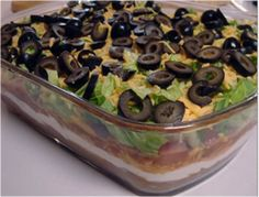 """Lowfat Mexican Layer Dip  Nothing says """"party"""" like this dip! Cut nearly 90% of fat from traditional calorie bomb using low fat or fat free refried beans & Greek yogurt. Add satisfying texture & color with a rainbow of veggies fresh chopped bell peppers, tomatoes, olives & lettuce. Dig in without the guilt celebrating Cinco de Mayo, or any summer picnic party like Memorial Day, July 4th, Labor Day…my birthday…hehehe"""